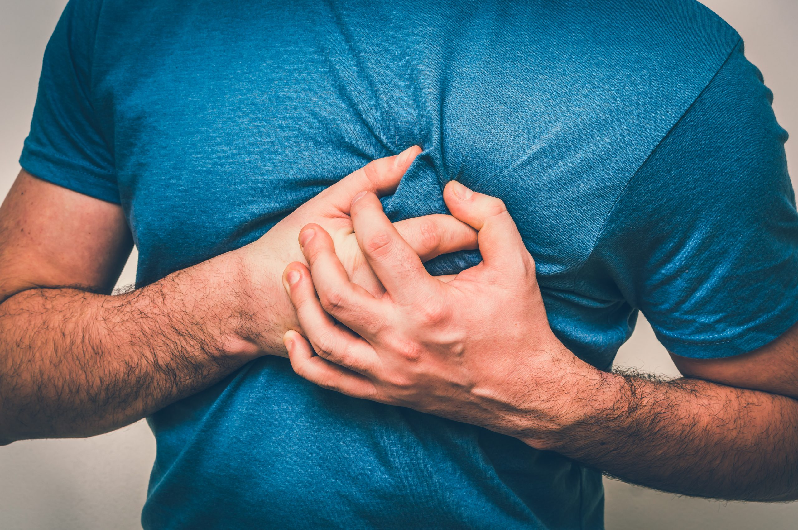 man holding chest due to pressure and pain related to heart attack